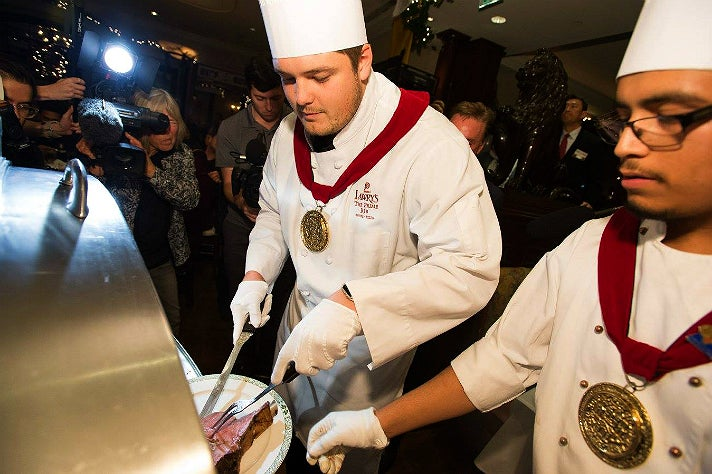Stanford offensive lineman Brendon Austin carves the first serving of prime rib at the 60th Lawry's Beef Bowl